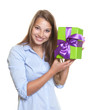 Attractive woman has a gift with ribbon in her hand