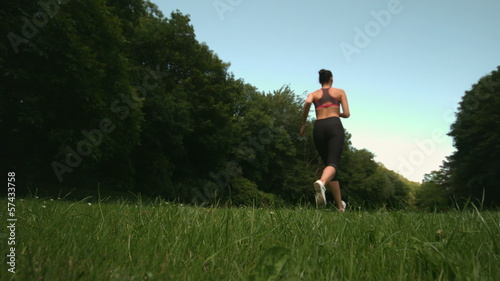 Low angle view of sporty womans back running on grass