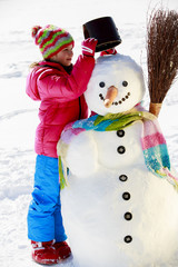 Winter fun, happy kid making snowman