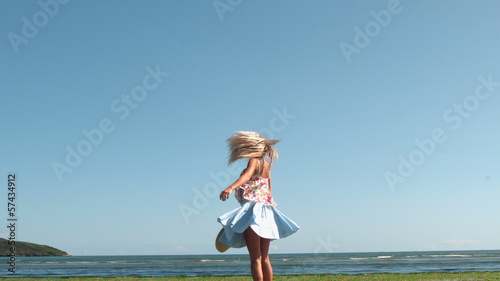 Gorgeous blonde holding straw hat spinning on beach