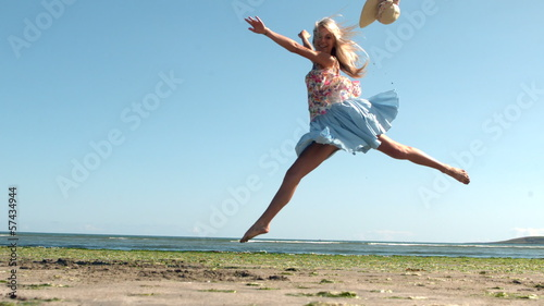 Attractive blonde doing ballet jump on beach