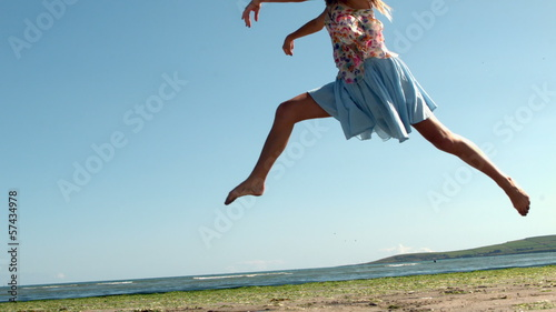 Gorgeous blonde doing ballet jump on beach