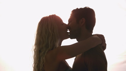 Couple kissing against sunlight