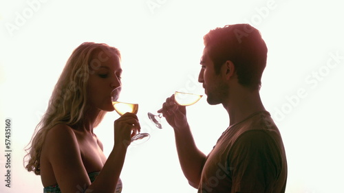 Couple drinking together against sunlight
