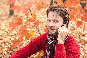 Smiling man talking on a mobile phone in an autumn park