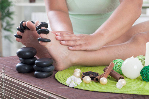 child foot ready to spa treatment with massage stones