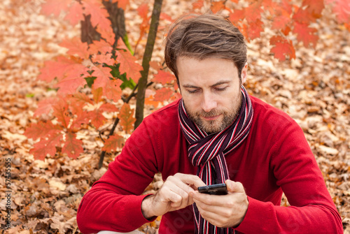 Man looking on a mobile phone in an autumn park
