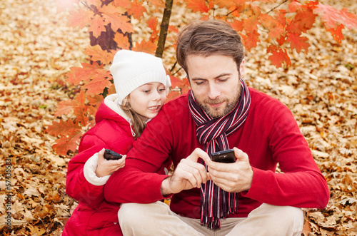 Father and daughter looking at phone in an autumn park
