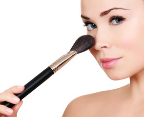 Beautiful woman doing make-up on face with cosmetic brush