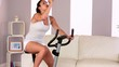 Active attractive brunette spinning on exercise bike