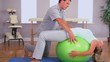 Physiotherapist working with a patient on an exercise ball