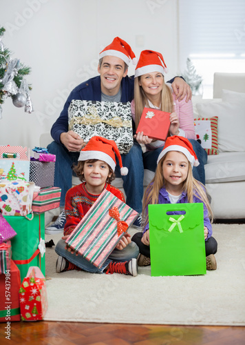 Family In Santa Hats Holding Christmas Gifts