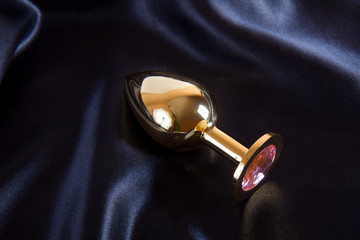 Golden butt plug sex toy on black