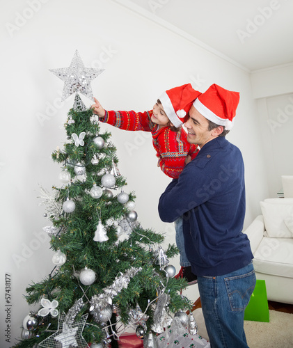 Son And Father Decorating Christmas Tree