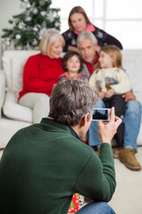 Man Photographing Family Through Smartphone
