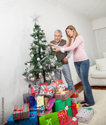 Senior Man And Daughter Decorating Christmas Tree