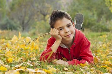 Niño tendido en el suelo cubierto de hojas otoñales