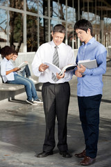 Teacher And Student Discussing Over Book On University Campus