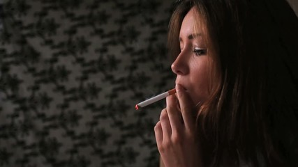 Attractive brunette smoking cigarette in dark room