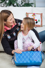Smiling Daughter And Mother Opening Christmas Gift