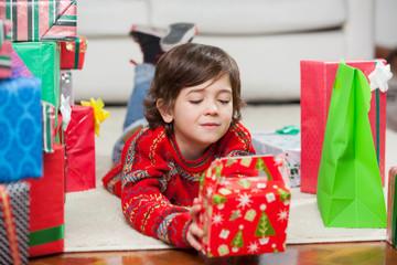 Boy With Christmas Present Lying On Floor
