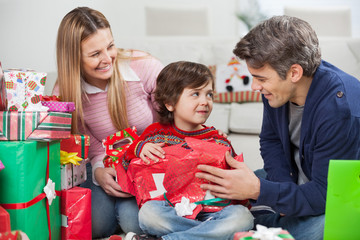 Parents With Son Opening Christmas Gift