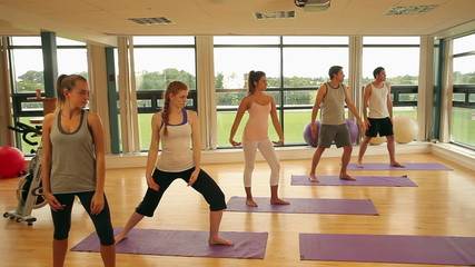 Fitness class and instructor doing yoga exercise