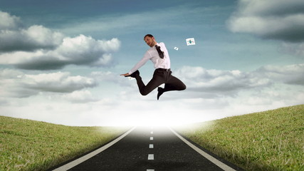 Businessman jumping in the air in front of flying sheets