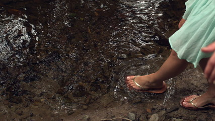 Close up of female feet dipping in water