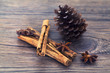 Star anise, cinnamon and pine cone on a wooden background