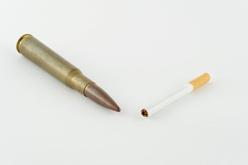 Cigaret and cartridge from fire-arms, it is isolated on a white