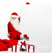 Santa Claus with sack full of gift boxes and blank notice board