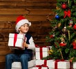 LIttle boy in Santa hat with gift box under christmas tree