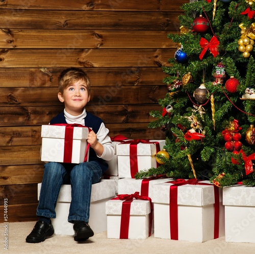 LIttle boy opening gift box under christmas tree