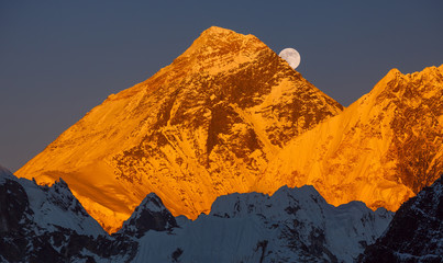 Gold pyramid of Mount Everest (8848 m) at sunset. Ascending moon