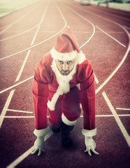 Santa Claus in the starting position on a running track