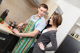 Man in apron cuts vegetables for dinner for his girlfriend