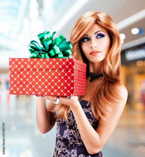 Bautiful woman holds the birthday gift red box
