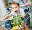 Boy sits in the shopping trolley with watermelon