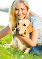 Woman embraces golden retriever lying on the grass