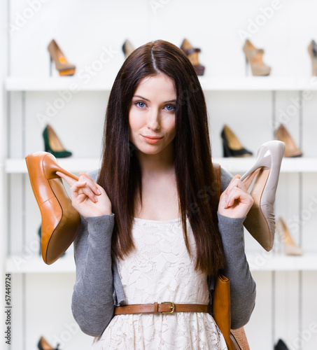 Woman keeps two heeled shoes in the shopping mall