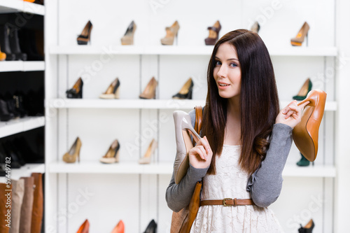 Woman holds two pumps in the shopping mall
