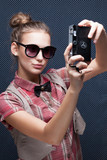 Portrait of trendy girl shooting autoportrait with retro camera