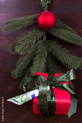 Rotes Geschenk mit Geldschein vor Tannenzweig mit roter Kugel