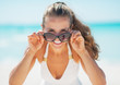 Smiling woman in swimsuit looking out from sunglasses on beach