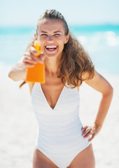 Happy young woman aiming bottle of sun block creme in camera