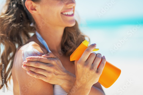 Closeup on smiling young woman applying sun block creme