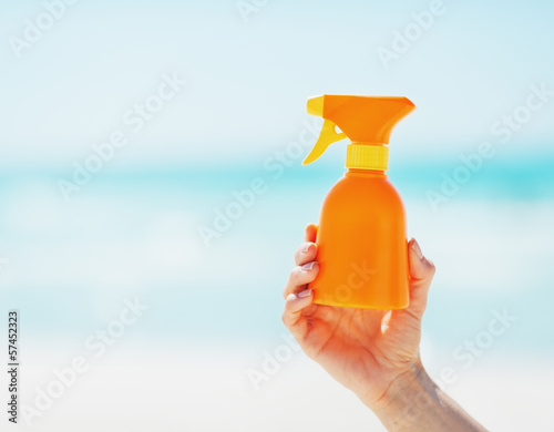 Closeup on bottle of sun screen creme in hand of woman