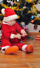 A boy opens a gift under the Christmas tree