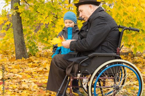 Disabled man and his grandson enjoying autumn